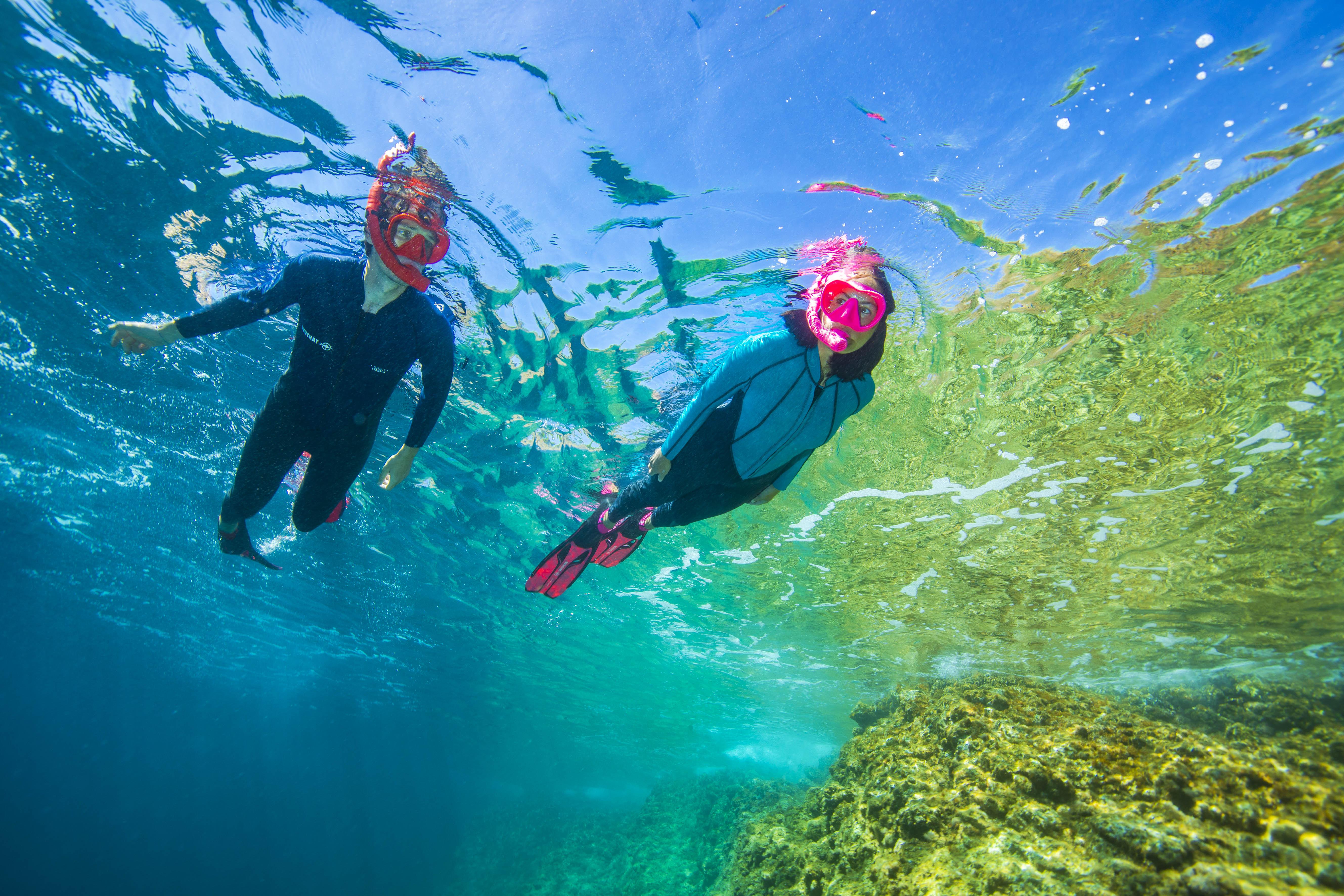 Un homme et une femme font une exploration sous-marine. Ils portent les combinaisons Atoll monopièce avec zip frontal. Ils ont chacun une paire de palmes, un masque Maxlux S et un tuba Spy Beuchat.